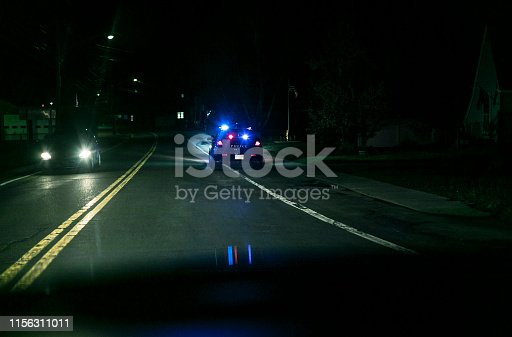 Night car driver personal perspective POV from behind while approaching a stationary police car with flashing emergency lights at the edge of a rural road. A car moving in the opposite direction is just passing the scene. The obscured car waiting up ahead of the police cruiser has been pulled over - presumably after a suspected traffic violation. Looks like someone has been caught in the act! (Vehicle details have been altered to make generic)