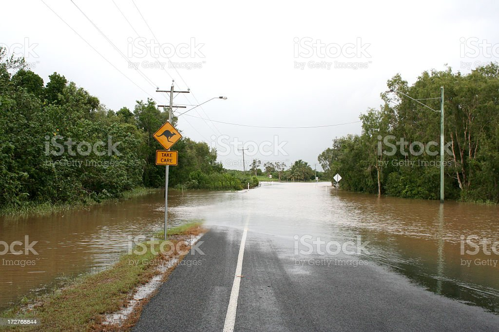 A roadside flooded with muddy water and a kangaroo sign stock photo