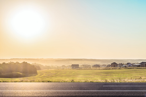 Roadside rural landscape in light of the low evening sun backlight. View from the road of a Russian village of bright sun. Sunny horizon with haze. Belgorod region.