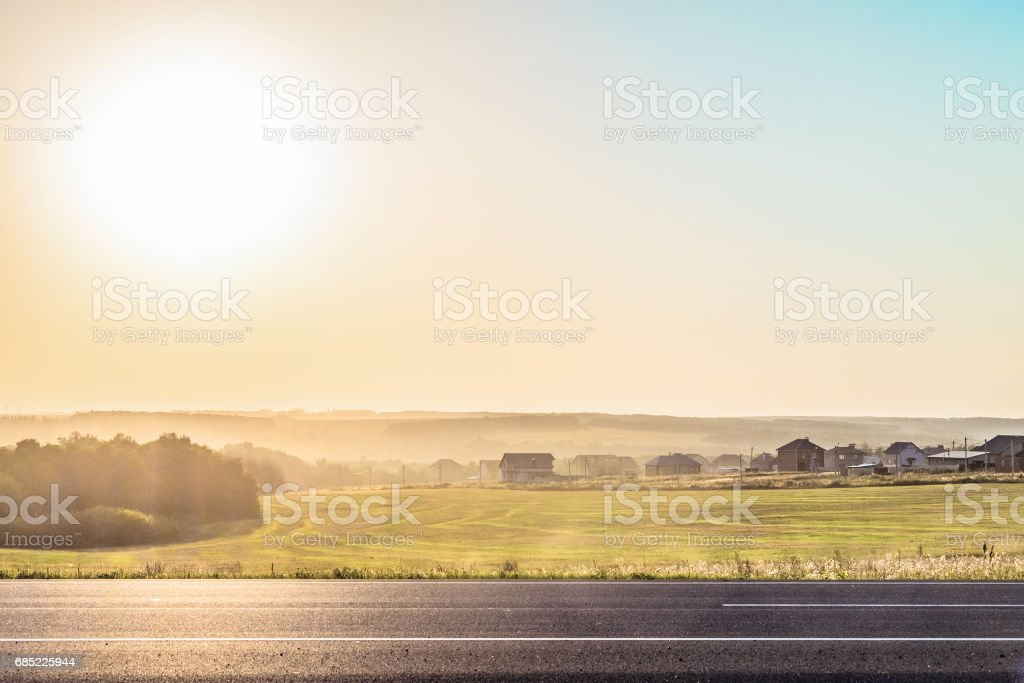 Roadside rural landscape in light of the low evening sun backlight. View from the road of a Russian village of bright sun. Sunny horizon with haze. Belgorod region. stock photo