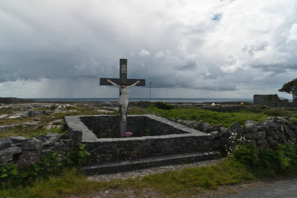 Roadside Shrine and Island Landscape, Inishmore, Aran Islands, County Galway, Ireland A roadside shrine on Cottage Road, Inishmore.  A large crucifix set with dry stone walls with cut flowers.  The walls are the native limestone.  It is a spring (early June) afternoon and there are fern and wildflowers.  The white flowers are Greater Burnet saxifrage (Scientific Name: Pimpinella major).  In the distance are more dry stone walls around fields, a stone shed, feeding horses and the sea, being Galway Bay, storm clouds with distant rain.  Aran Islands, County Galway, Ireland. michael stephen wills aran stock pictures, royalty-free photos & images