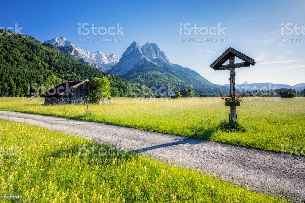 Roadside Shrine on flower meadow in front of Zugspitze - Garmisch Partenkirchen stock photo