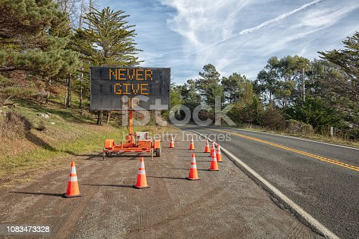 NEVER GIVE UP::  This is a photograph of a mobile roadside sign parked on highway one in northern California. It is a trailer and powered by batteries and provides information and warnings for drivers by displaying words on a large panel display.