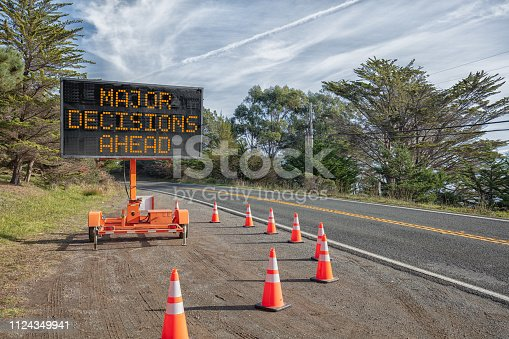 DECISIONS AHEAD: This is a photograph of a mobile roadside sign parked on highway one in northern California. It is a trailer and powered by batteries and provides information and warnings for drivers by displaying words on a large panel display.