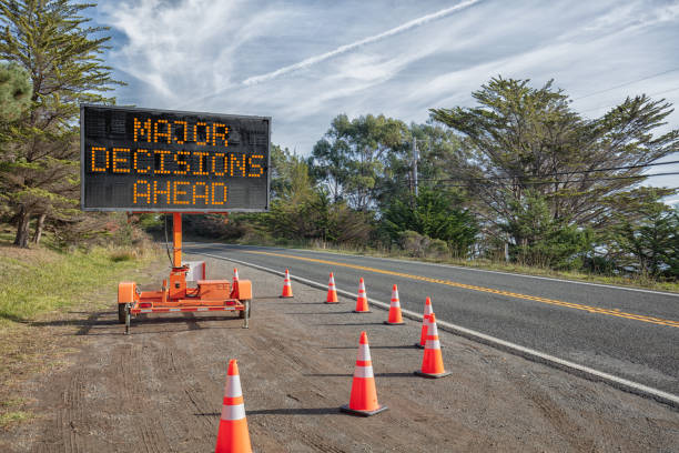 DECISIONS AHEAD: Roadside sign: Trailer mobile warning sign parked by road with words for safety by orange cones DECISIONS AHEAD: This is a photograph of a mobile roadside sign parked on highway one in northern California. It is a trailer and powered by batteries and provides information and warnings for drivers by displaying words on a large panel display. road warning sign stock pictures, royalty-free photos & images