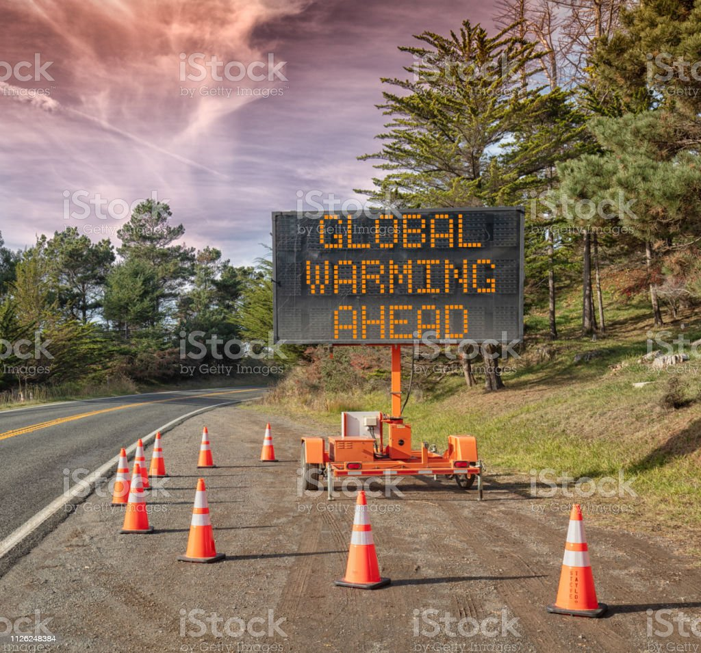 GLOBAL WARMING AHEAD: Roadside sign: Trailer mobile warning sign parked by road with words for safety by orange cones Global  Warming AHEAD:  This is a photograph of a mobile roadside sign parked on highway one in northern California. It is a trailer and powered by batteries and provides information and warnings for drivers by displaying words on a large panel display. Adversity Stock Photo