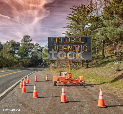 Global  Warming AHEAD:  This is a photograph of a mobile roadside sign parked on highway one in northern California. It is a trailer and powered by batteries and provides information and warnings for drivers by displaying words on a large panel display.