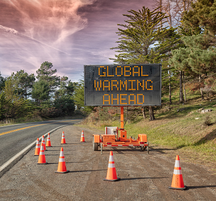 Global Warming Ahead Roadside Sign Trailer Mobile Warning Sign Parked By Road With Words For Safety By Orange Cones Stock Photo - Download Image Now