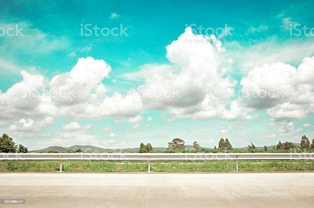 Roadside view with green hill, clouds & sky stock photo