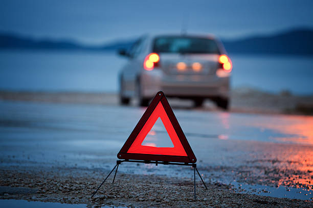 A roadside warning triangle and car with lights on wet road stock photo