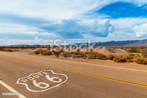 U.S. Route 66 highway, with sign on asphalt and a long train in the background, near amboy, california. Located in the mojave dessert. Photo made on a motorcycle roadtrip.