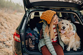 Photo of a young smiling woman and her dog sitting the trunk of a car on a beautiful autumn day; taking a short break during their road trip.
