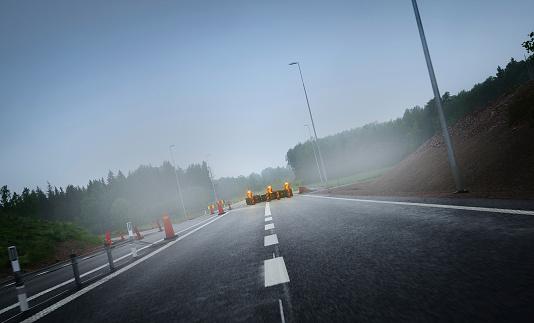 Roadwork ongoing,  closed lane. Fog.
