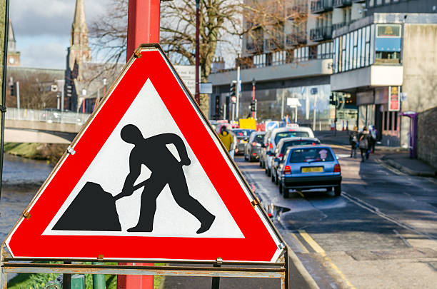 Roadworks Sign on a Busy Street in Inverness, Scotland European Roadworks Sign on a Busy Street in Inverness, Scotland. Some blurred cars, stuck in traffic because of the roadworks, are in background. inverness scotland stock pictures, royalty-free photos & images