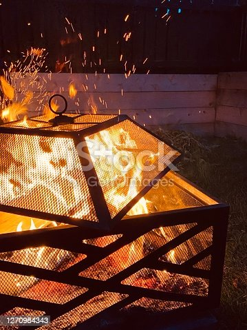 Sparks shoot out of hot flames that are burning in a black metal fire pit.