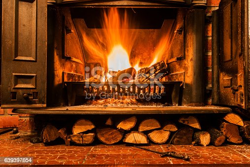 Roaring fire in an arched stone fireplace, Cozy blazing fire in fireplace