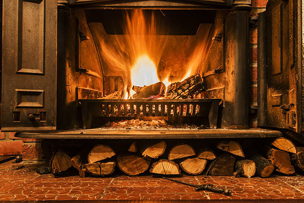Roaring fire in an arched stone fireplace Roaring fire in an arched stone fireplace, Cozy blazing fire in fireplace log fire stock pictures, royalty-free photos & images