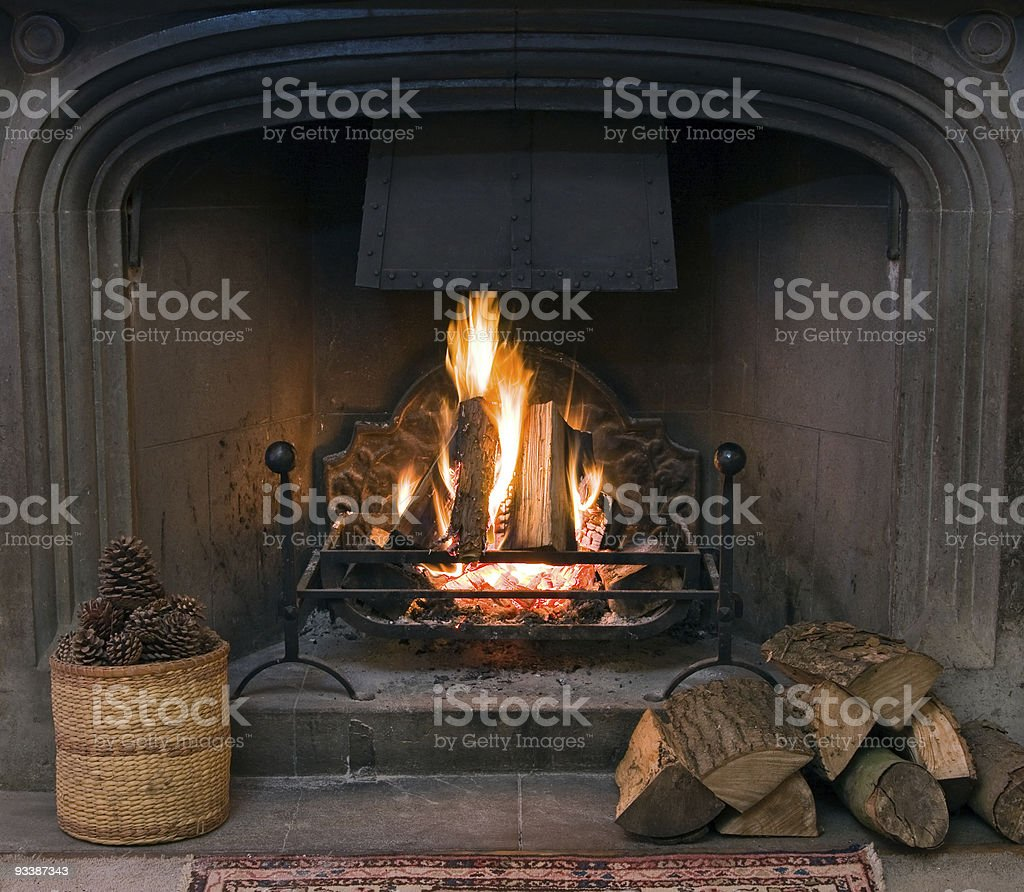 Roaring fire in an arched stone fireplace stock photo
