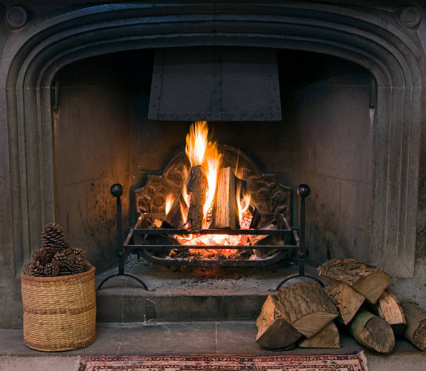 Roaring fire in an arched stone fireplace  log fire stock pictures, royalty-free photos & images