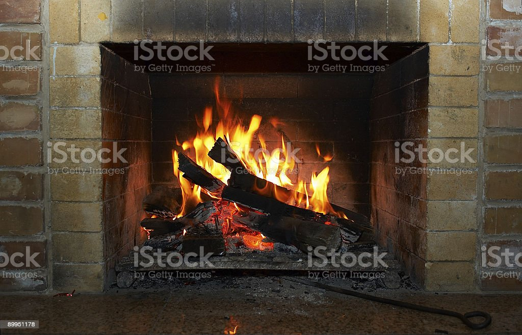 A roaring fireplace with a brick surround stock photo