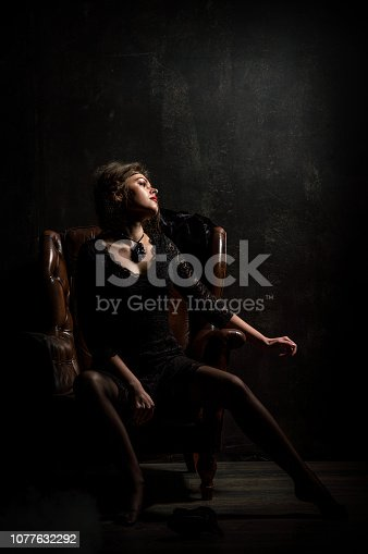 Roaring Twenties. Woman portrait in the style of Gatsby. Low key. A beautiful young woman in a black lace dress is sensually sitting in a brown leather chair. Black background.