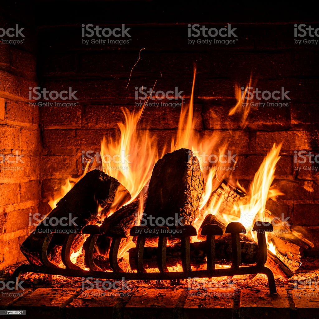 A roaring wood burning fire in the fireplace stock photo