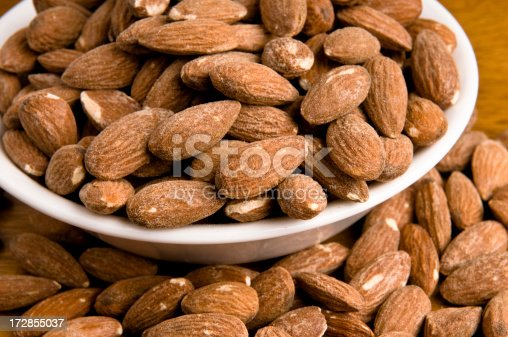 Fresh dry roasted salted almonds in bowl on table