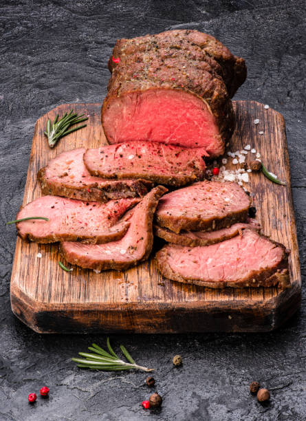 Roast beef on cutting board with salt and pepper. stock photo