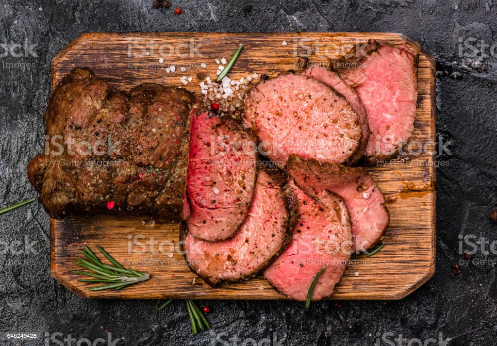 Roast beef on cutting board with salt and pepper. Top view. stock photo