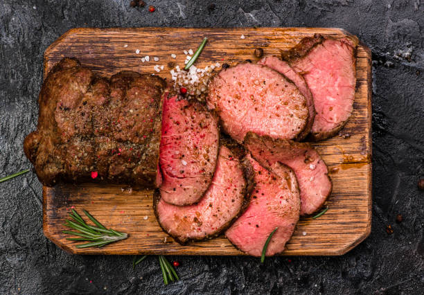 Roast beef on cutting board with salt and pepper. Top view. Roast beef on cutting board with salt and pepper. Top view. roast beef stock pictures, royalty-free photos & images