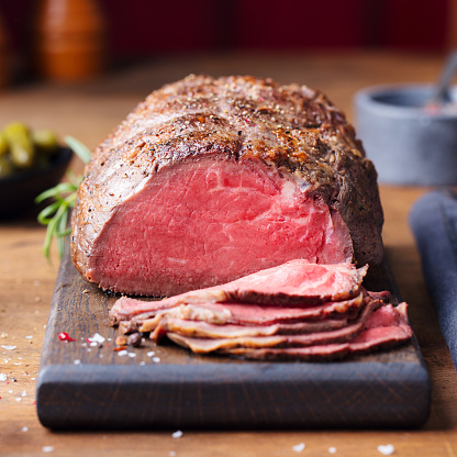 Roast beef on cutting board. Wooden background. Close up