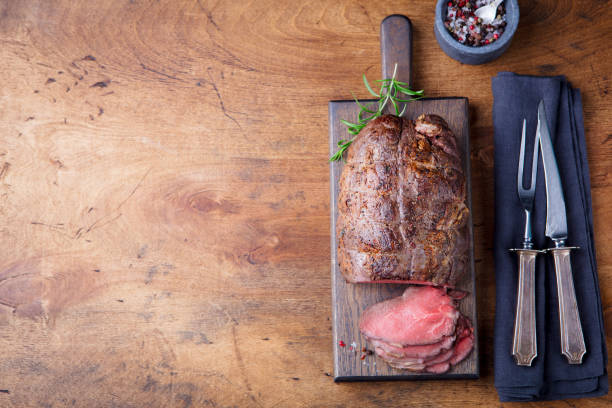 Roast beef on cutting board. Wooden background. Top view. Copy space. Roast beef on cutting board. Wooden background. Top view. Copy space roast beef stock pictures, royalty-free photos & images