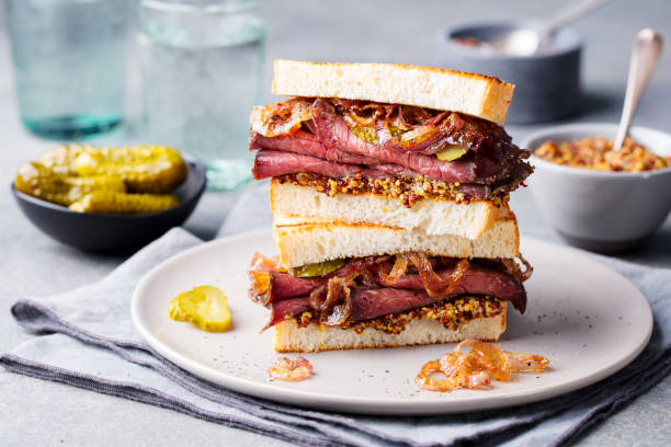 roast beef sandwich on a plate with pickles. - food styling stock photos and pictures