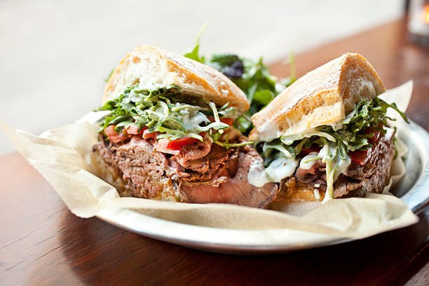 "Roast beef sandwich ""Freshly roasted beef sliced very thin and piled high onto a sweet baguette; served with organic greens, caramelized onions, peppers and horseradish aioli."" horseradish stock pictures, royalty-free photos & images"
