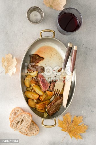 808351132 istock photo Roast beef steak with fried potatoes in garlic sauce in copper pan on light stone surface with red wine, top view 840751344