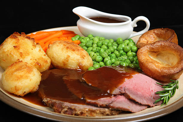roast beef with a side of peas and carrots - gebraden vlees stockfoto's en -beelden