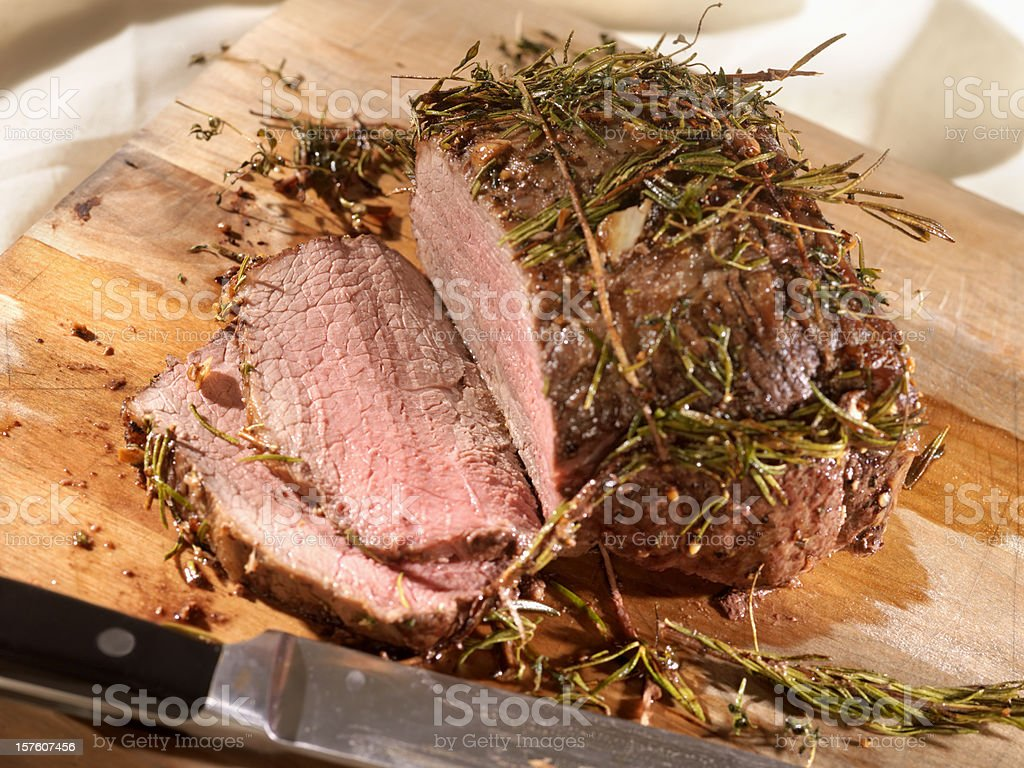 Roast Beef with Rosemary on a Cutting Board royalty-free stock photo