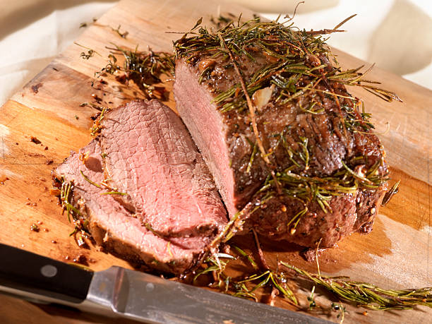 Roast Beef with Rosemary on a Cutting Board  roast beef stock pictures, royalty-free photos & images