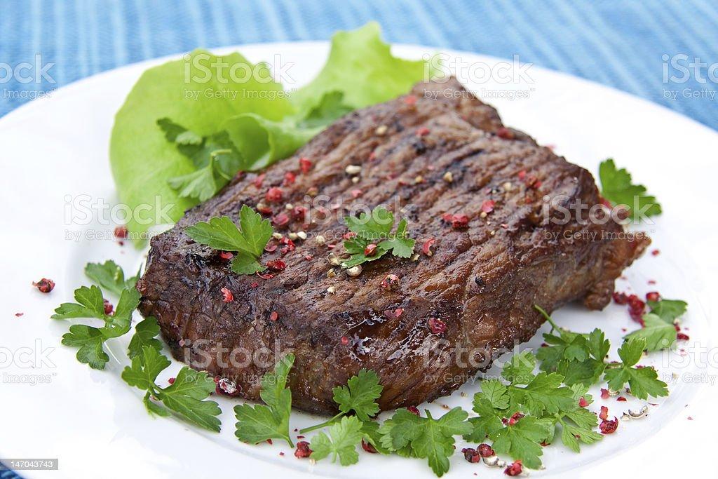 roast big steak on green dish close up stock photo