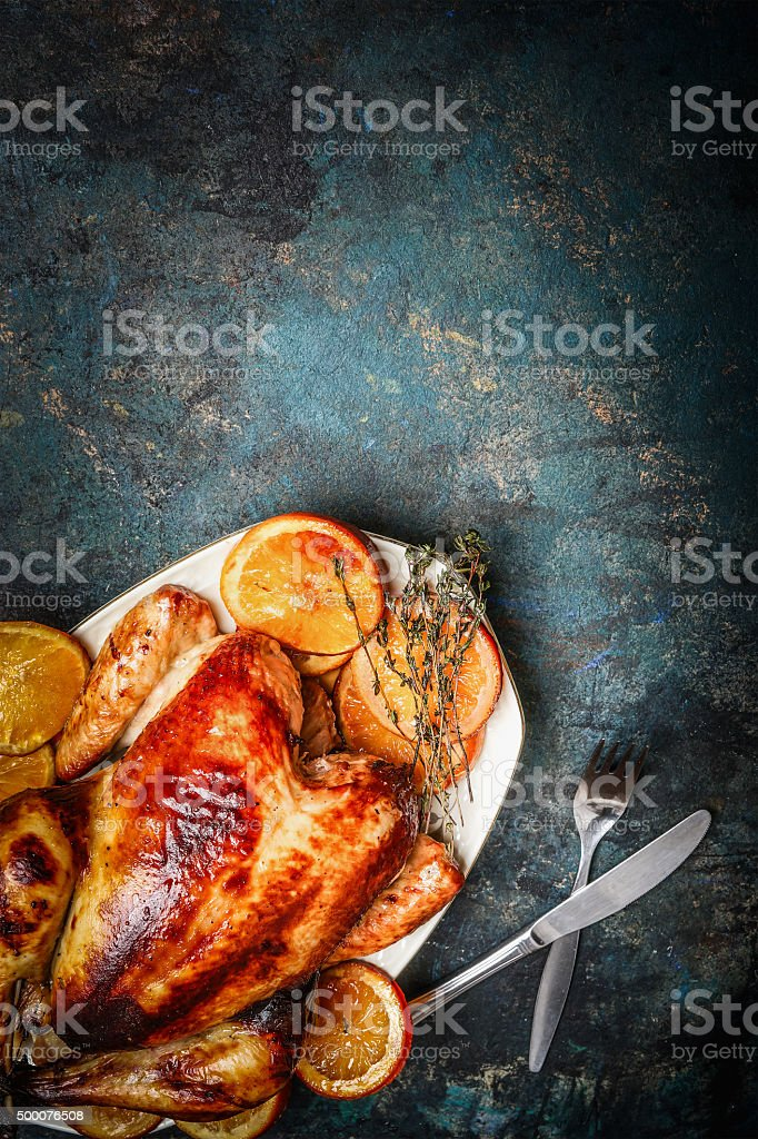 Roast chicken and orange slices served with fork , knife stock photo