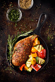 Roast chicken breast with grilled vegetables in a cast iron skillet