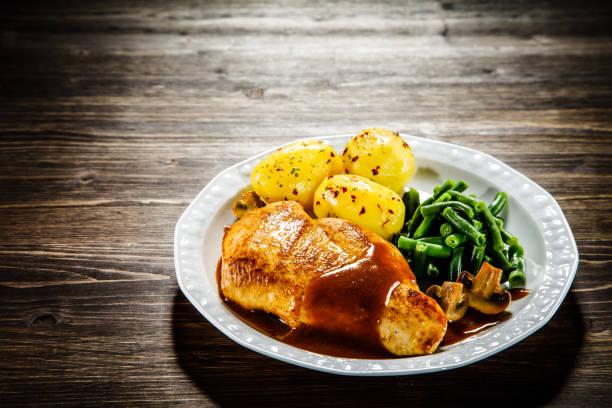 gebratene hähnchenbrust in soße, kartoffeln und gemüse - salzkartoffel stock-fotos und bilder