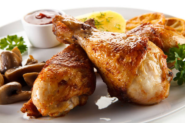 Roast chicken drumsticks with boiled potatoes and vegetables stock photo