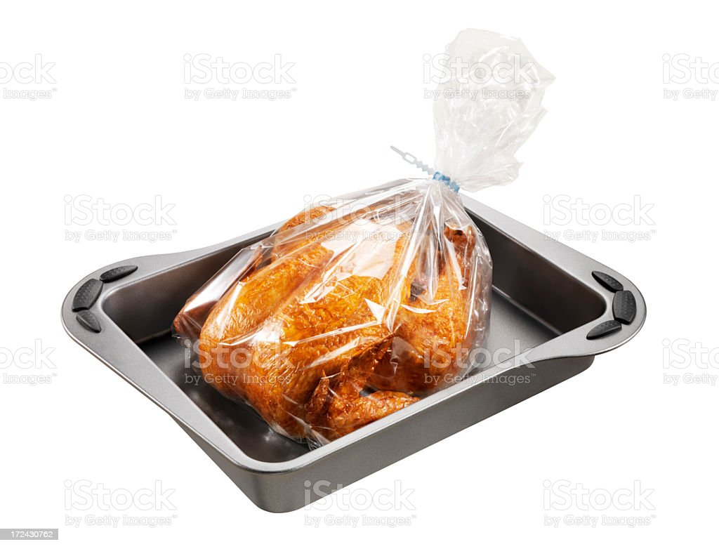 Roast chicken in a plastic bag over a cooking tray royalty-free stock photo