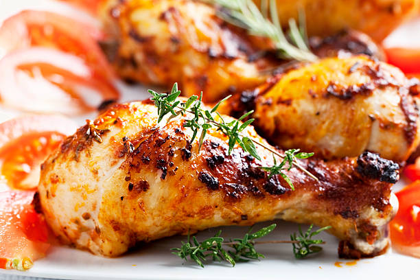 roast chicken legs and rosemary roast chicken legs, decorated with slices of tomato on a white plate, perfect food for  a warm summer evening drumstick stock pictures, royalty-free photos & images