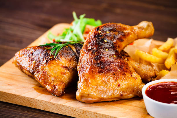Roast chicken legs with fried potatoes and vegetables stock photo