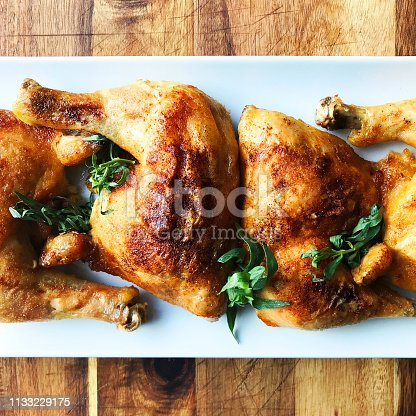 Roast Chicken Quarters on White Plate and Cutting Board
