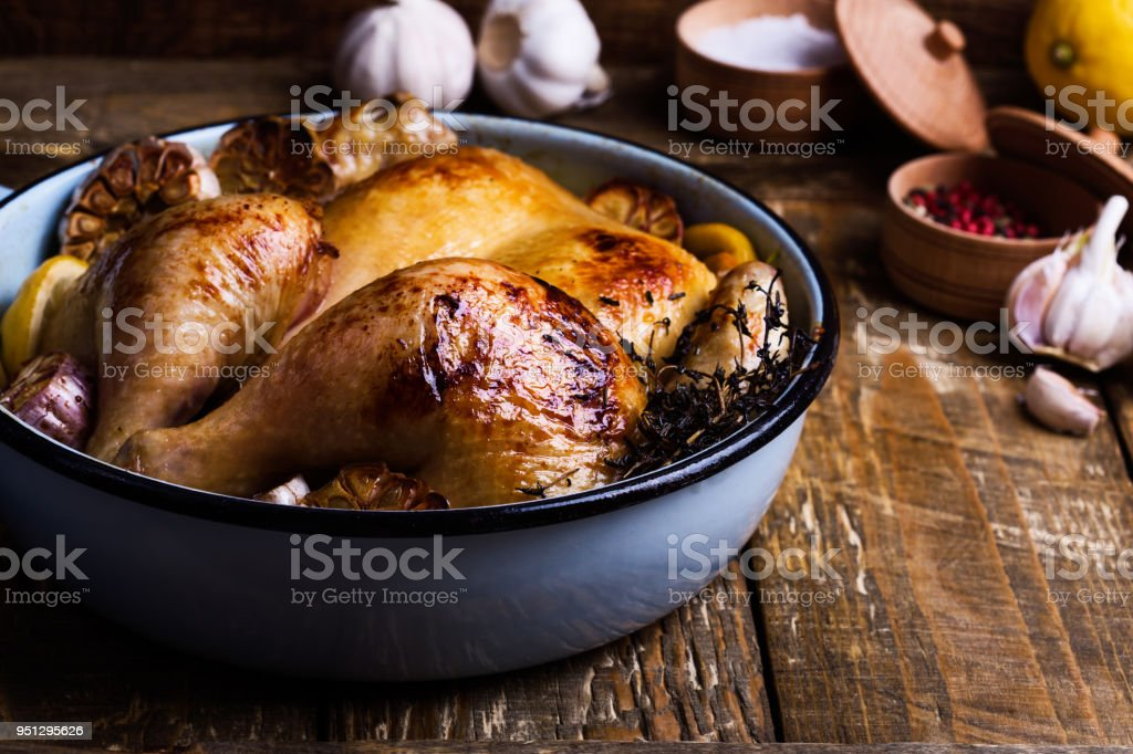 Roast chicken with garlic, thyme and lemon in cooking pan stock photo