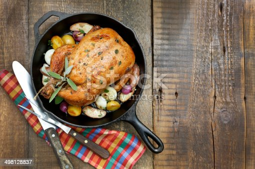 A overhead view of a roast chicken on a rustic wood table top.