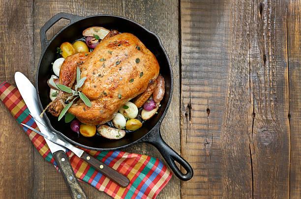 gebratenes huhn mit kartoffeln und zwiebeln in gusseisen pfanne. - perlzwiebeln stock-fotos und bilder